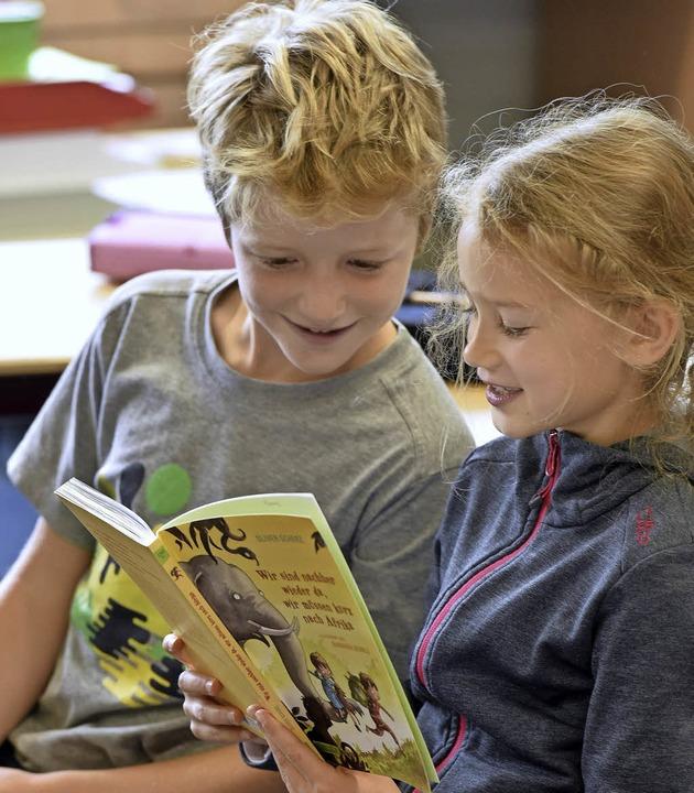 Finn (links) und Sophia lesen vor aus dem Afrika-Buch von Oliver Scherr.  | Foto: Thomas Kunz