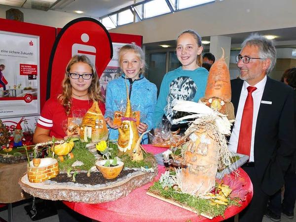 Dieter Köpfler (rechts) gratulierte den drei Erstplatzierten des  Runkele-Schnitz-Wettbewerbs (von links): Katharina Martin (3.),  Felicitas Meier (2.) und Melina Metzler (1.).