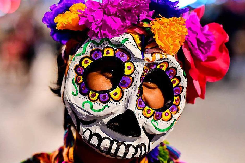 """Bunte Totenköpfe und Riesenblumen im Haar. Die Catrina-Parade steht unter dem Motto """"Der elegante Tod"""" und besticht durch kreative Kostüme. Gruselig wirkt das ganze indes nicht. (Foto: AFP)"""