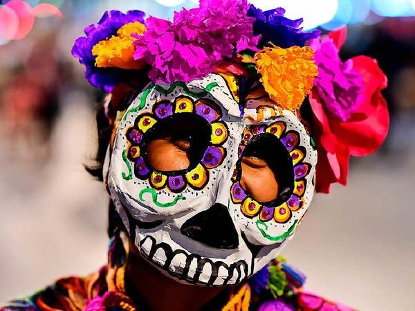 """Bunte Totenköpfe und Riesenblumen im Haar. Die Catrina-Parade steht unter dem Motto """"Der elegante Tod"""" und besticht durch kreative Kostüme. Gruselig wirkt das ganze indes nicht."""