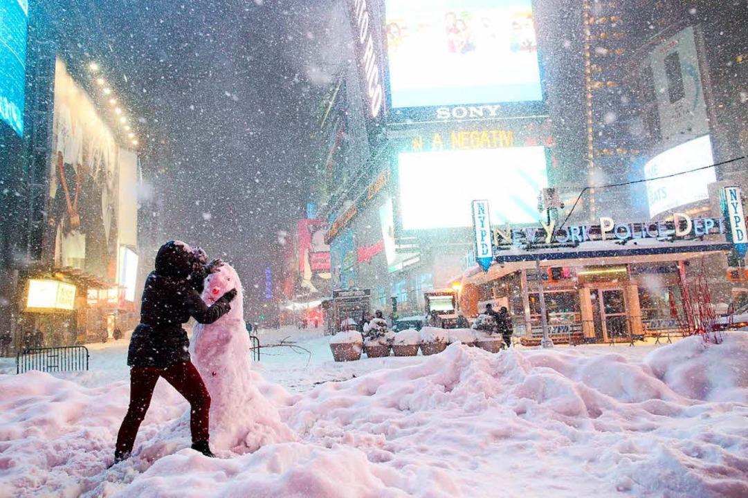 Eine Frau dekoriert in New York einen Schneemann auf dem Times Square.  | Foto: AFP