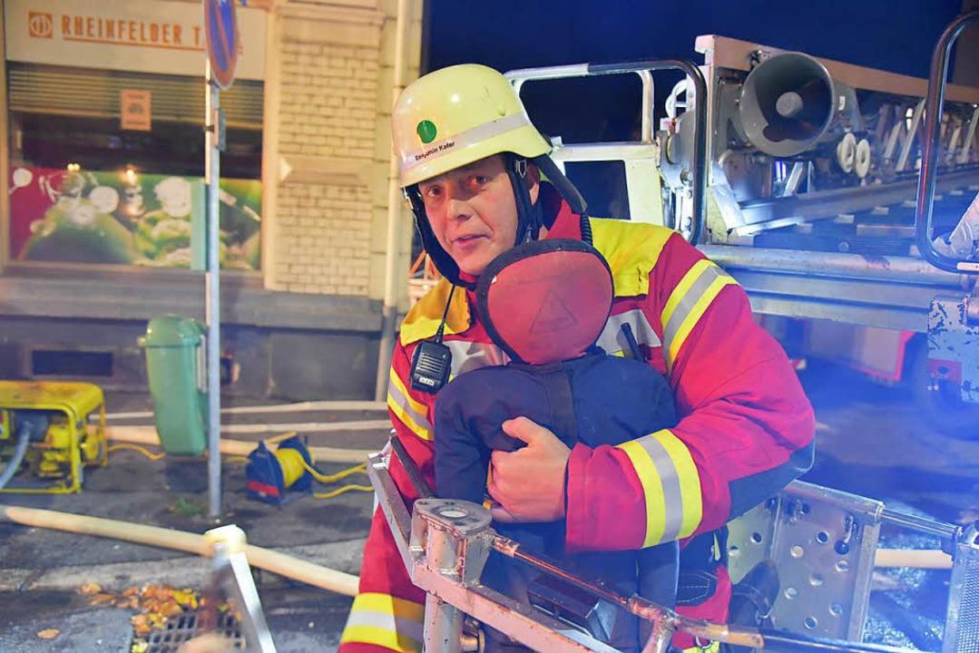 """Ein Feuerwehrmann mit dem vermissten """"Kind""""    Foto: Martin Eckert"""