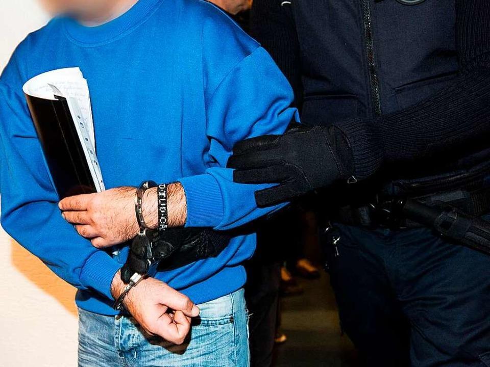 Der Angeklagte Catalin C. wird von ein...es Landgerichtes in Freiburg gebracht.  | Foto: dpa
