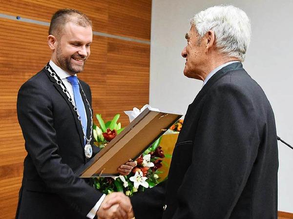 Merzhausens Bürgermeister Christian Ante überreicht Eugen Isaak die Urkunde.