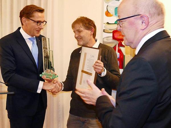 Günther Schmidt nimmt für die IG Spielplatz Schwedenstraße die Urkunde und Glasstele in Empfang. Links: Stiftungsratsvorsitzender Rainer Liebenow, rechts Norbert Dietrich, Vorsitzender der Bürgerstiftung.
