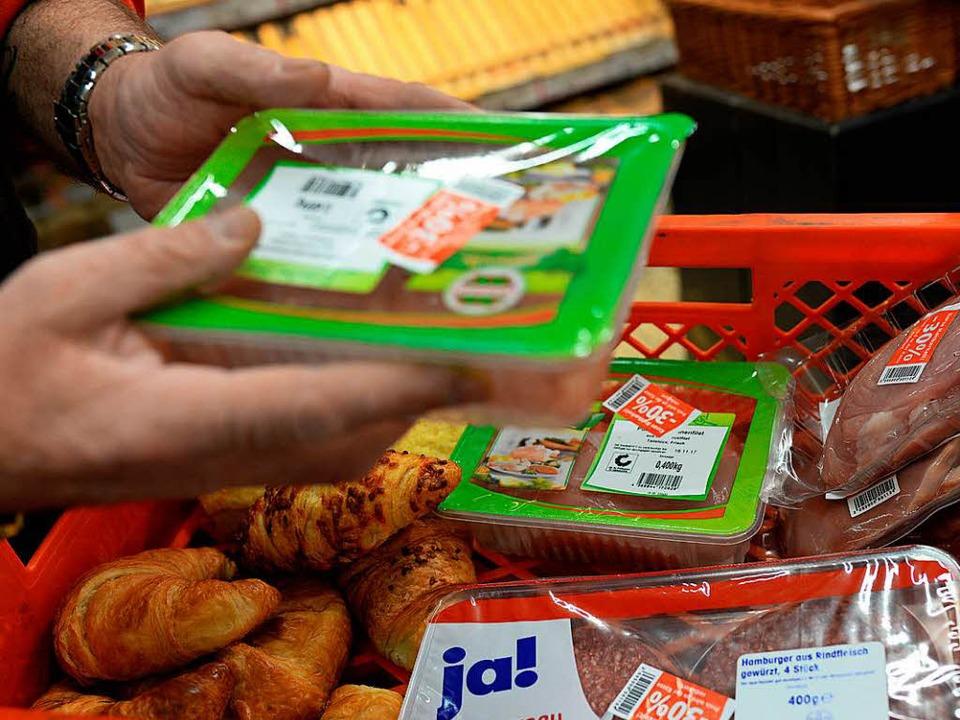 Marktleiter Gerhard Surges packt in Tr...bieten sie Bedürftigen zum Verzehr an.  | Foto: dpa