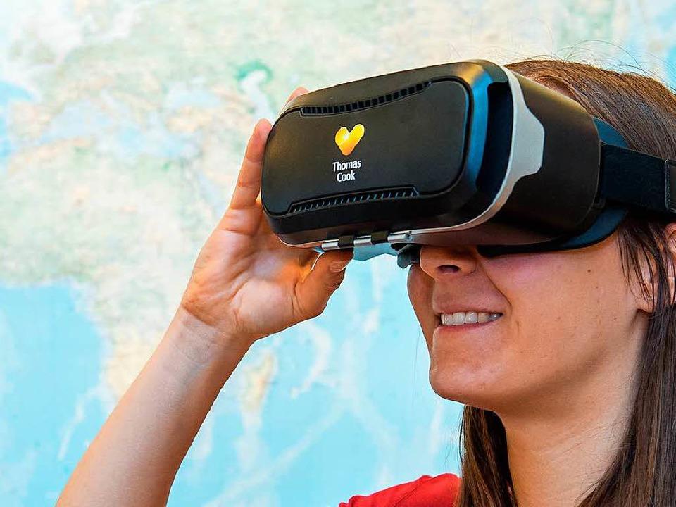 Eine Frau setzt in einem Reisebüro in Hannover eine VR-Brille auf.  | Foto: dpa