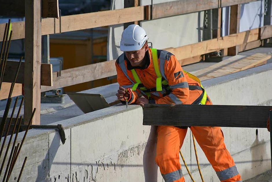 Ein Mitarbeiter hält auf dem Bauwerk einen Spiegel in Position, damit sein Kollege die genaue Position bestimmen kann. (Foto: Hannes Lauber)
