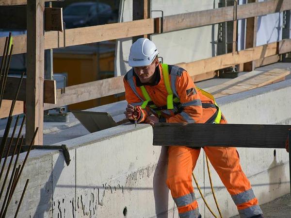 Ein Mitarbeiter hält auf dem Bauwerk einen Spiegel in Position, damit sein Kollege die genaue Position bestimmen kann.