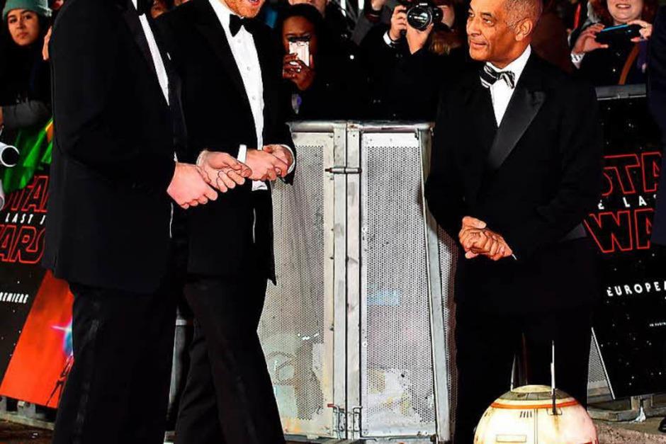 Die britischen Prinzen William (l) und Harry (M) nehmen den Droiden BB-8 unter die Lupe. (Foto: dpa)