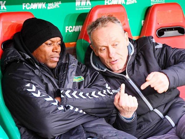 Christian Streich erklärt vor der Partie gegen den FC Augsburg Karim Guédé etwas.