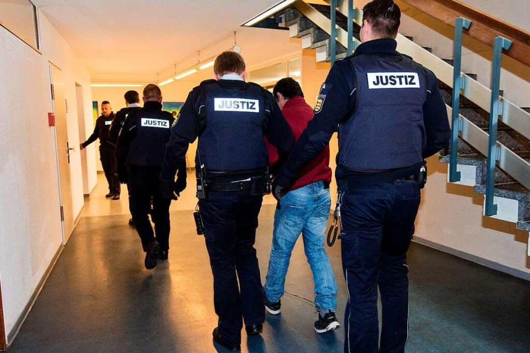 Catalin C. wird nach der Urteilsverkün...beamten aus dem Gerichtssaal gebracht.  | Foto: dpa