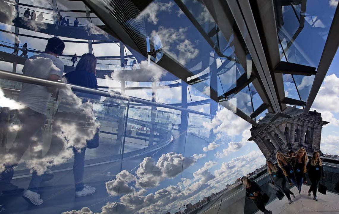 Wolken spiegeln sich in Berlin im Glas der Reichstagskuppel.   | Foto: dpa