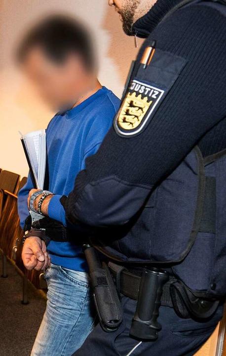 Ein Polizist bringt den Angeklagten Catalin C. in den Gerichtssaal.     Foto: dpa