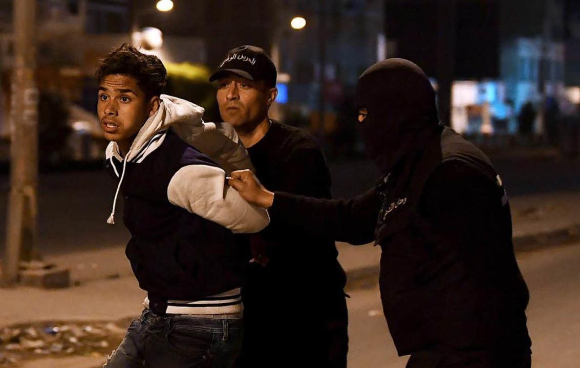 Sicherheitskräfte nehmen einen Demonst...ßenbezirken der Hauptstadt Tunis fest.  | Foto: AFP