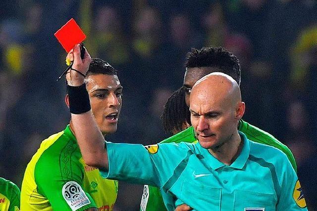 Schiedsrichter tritt Spieler und zeigt ihm die gelb-rote Karte