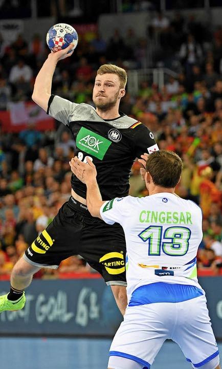 Philipp Weber (l) wirft den Ball über Sloweniens Darko Cingesar.     Foto: DPA