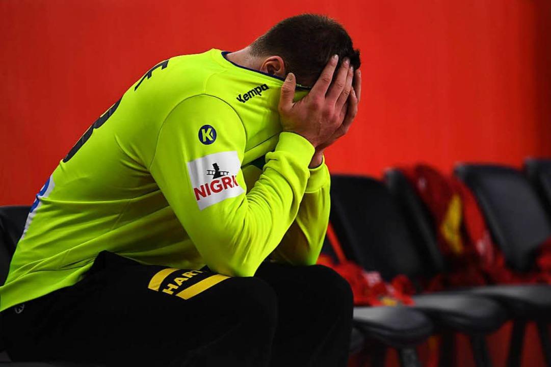 Andreas Wolff vergräbt das Gesicht in seinem Trikot.  | Foto: dpa