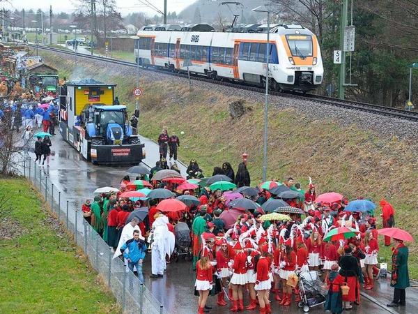 Das Bild des Tages vom Fasnachtszug in Münstertal: Regenschirme auf dem neuen Zugweg entlang der Müsntertalbahn