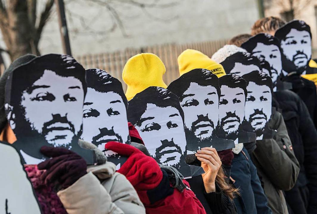 Auf den Masken, die sich die demonstri...mit ihren Protesten seine Freilassung.  | Foto: dpa