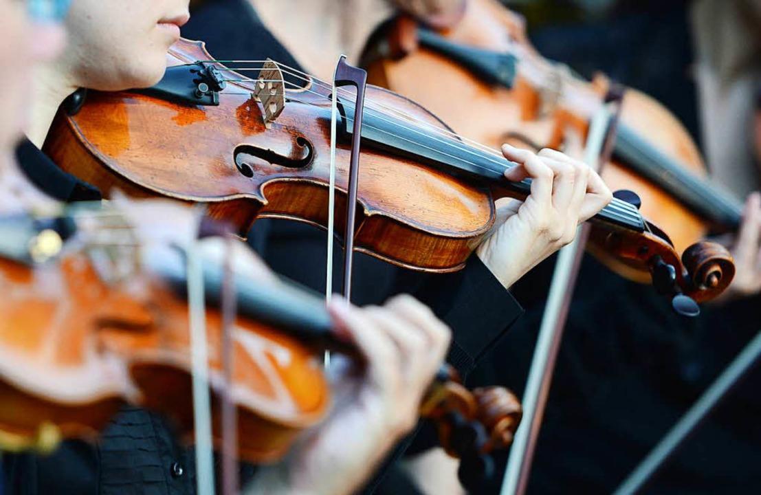 Die Geiger sitzen in einem Orchester beisammen.   | Foto: dpa