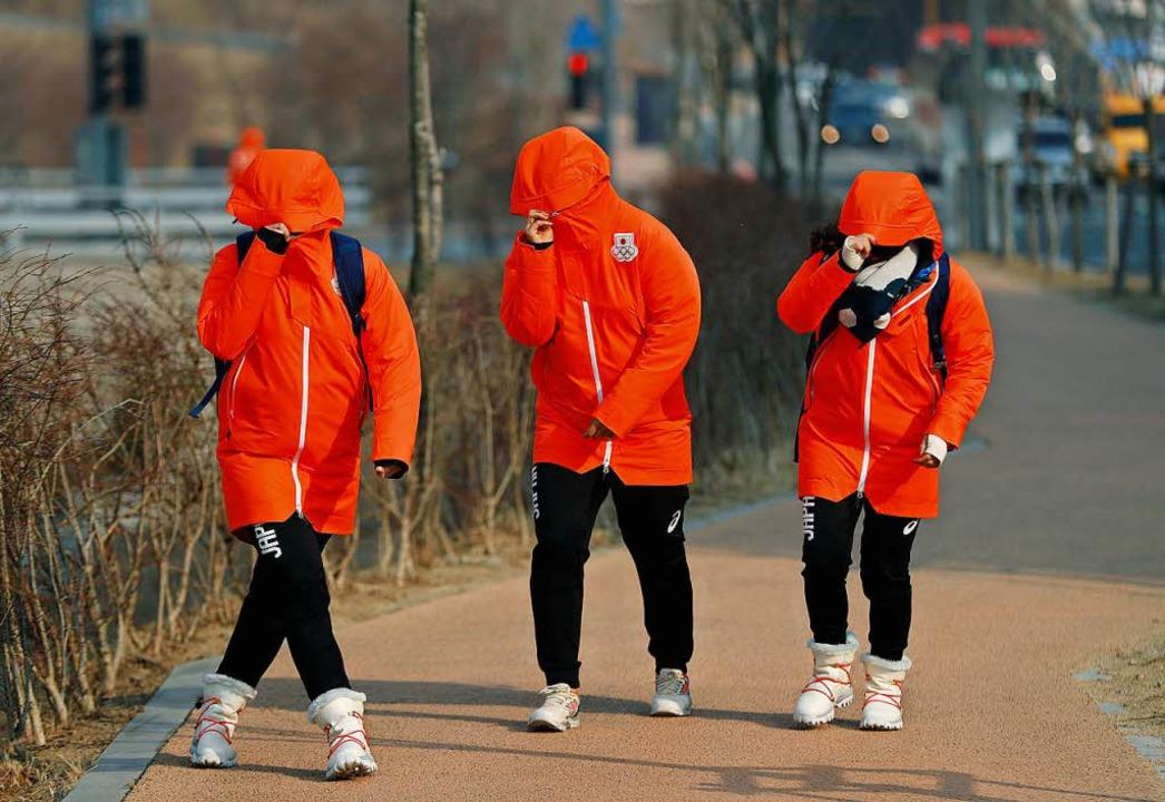 Mitglieder des japanischen Teams schüt...Wind auf dem Weg zum Olympischen Dorf.  | Foto: dpa
