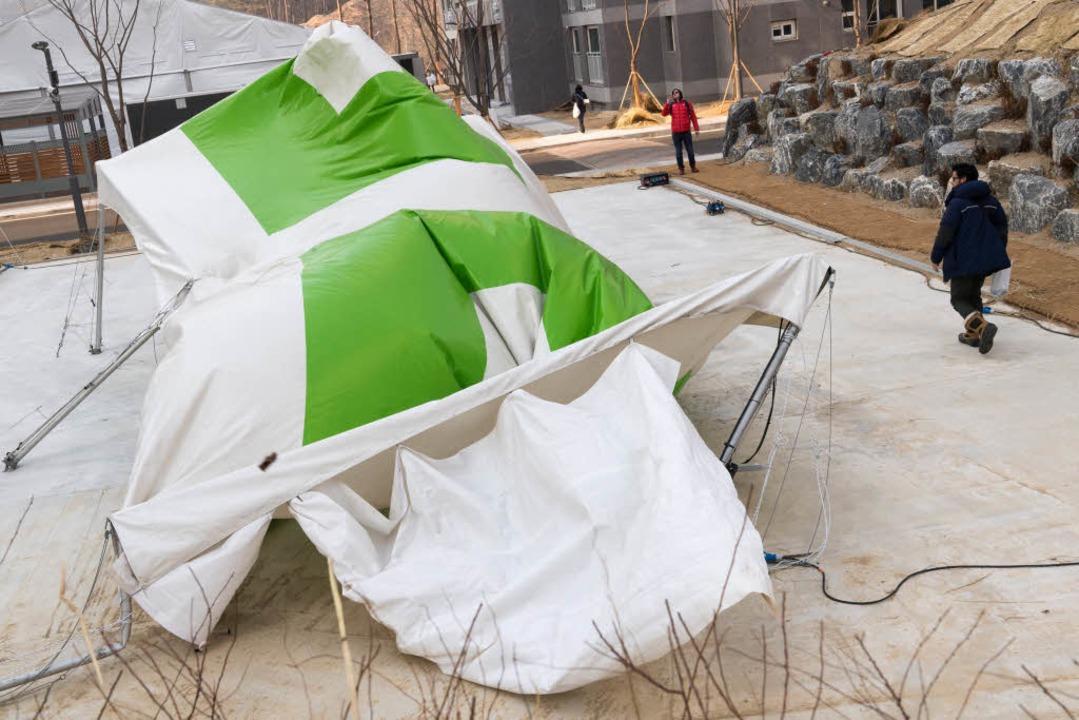 Ein vom starken Wind zerstörtes Zelt liegt im Mediendorf.  | Foto: dpa
