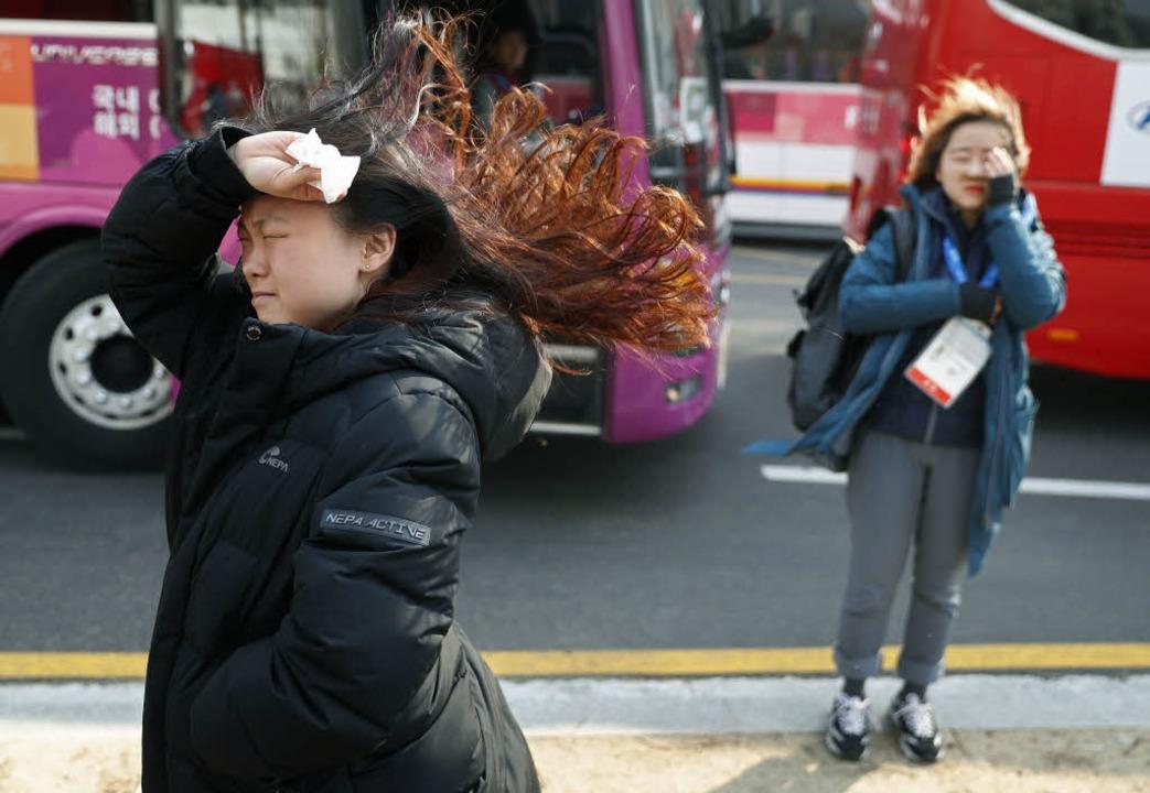 Menschen kämpfen gegen den starken Wind.  | Foto: dpa