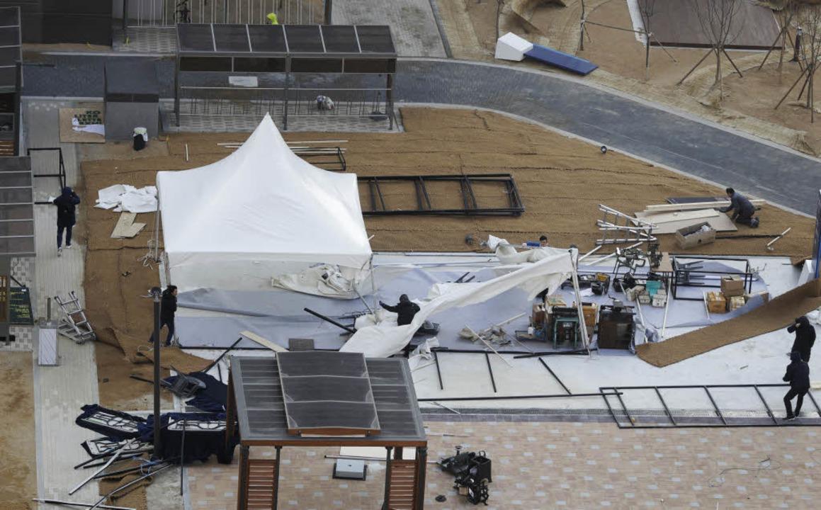 Arbeiter sichern ein vom starken Wind zerstörtes Zelt im Mediendorf.  | Foto: dpa
