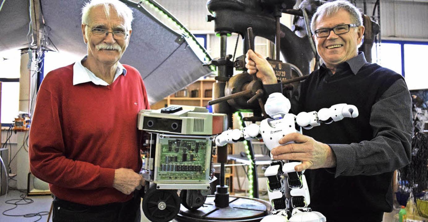 Vereinsvorsitzender Frank Leonhardt (r...r Schemitz mit einem älteren Roboter.   | Foto: J. Trauden