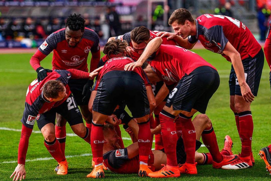 Nürnbergs Hanno Behrens (unten) wird v... Team für seinen 2:0-Treffer gefeiert.  | Foto: dpa