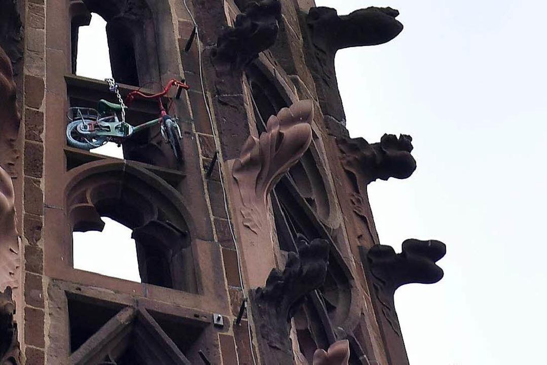 Das Kinderfahrrad hängt mit einer Eisenkette im Turmhelm.  | Foto: Thomas Kunz