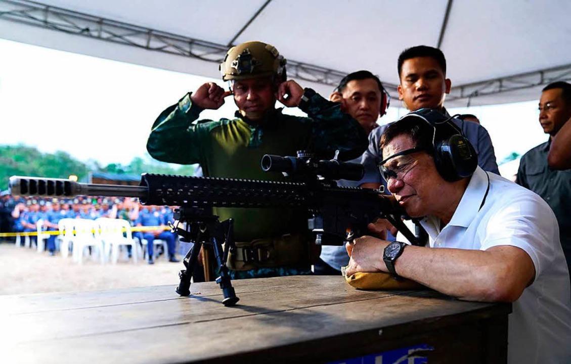 Der philippinische Staatschef Rodrigo Duterte versucht sich im Schießen.  | Foto: AFP