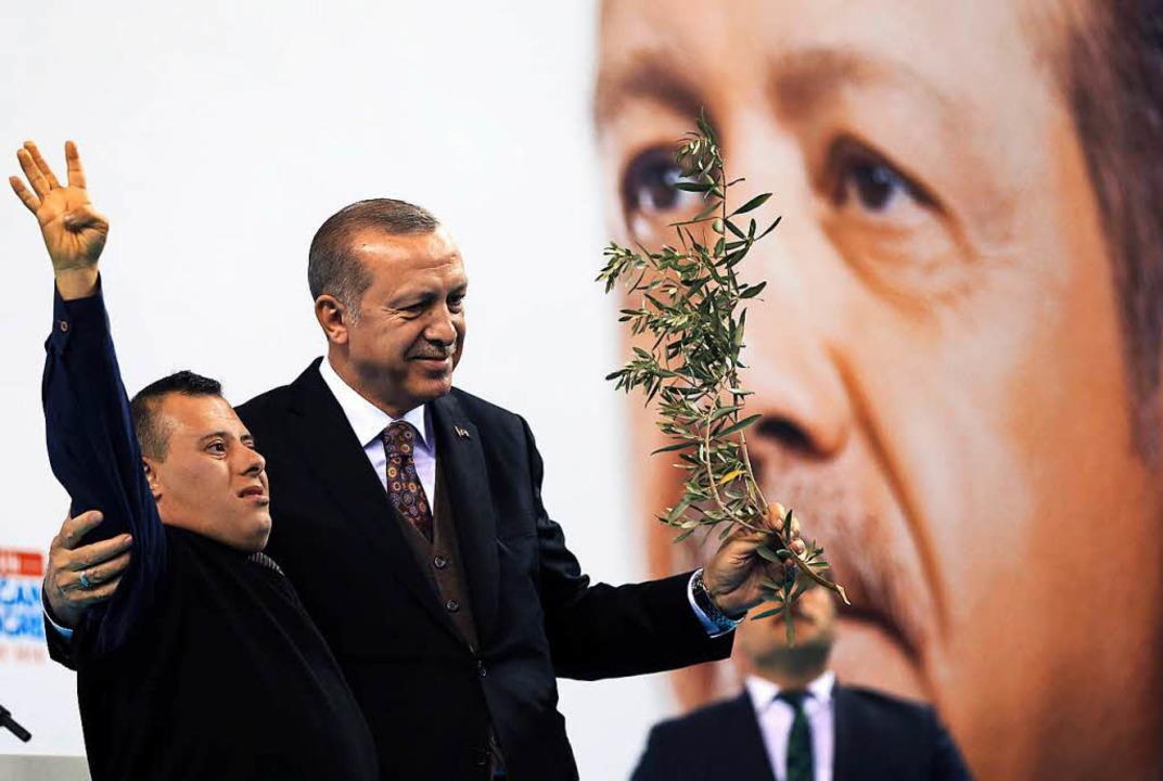 Der türkische Präsident Erdogan umarmt einen Unterstützer.  | Foto: DPA