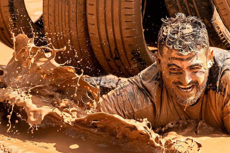 """Beim """"Mud Day Race"""" überwinden die Teilnehmer Hindernisse über 13 Kilometer – und kriechen dabei durch jede Menge Schlamm. (Foto: AFP)"""
