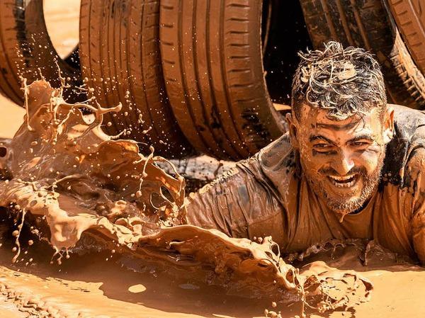 """Beim """"Mud Day Race"""" überwinden die Teilnehmer Hindernisse über 13 Kilometer - und kriechen dabei durch jede Menge Schlamm."""