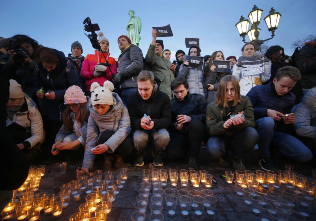 Menschen zünden im Stadtzentrum von Mo...m in Kemerowo für die Opfer Kerzen an.  | Foto: dpa