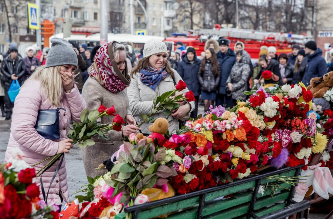 Trauernde legen Blumen nieder in Kemerowo.  | Foto: dpa
