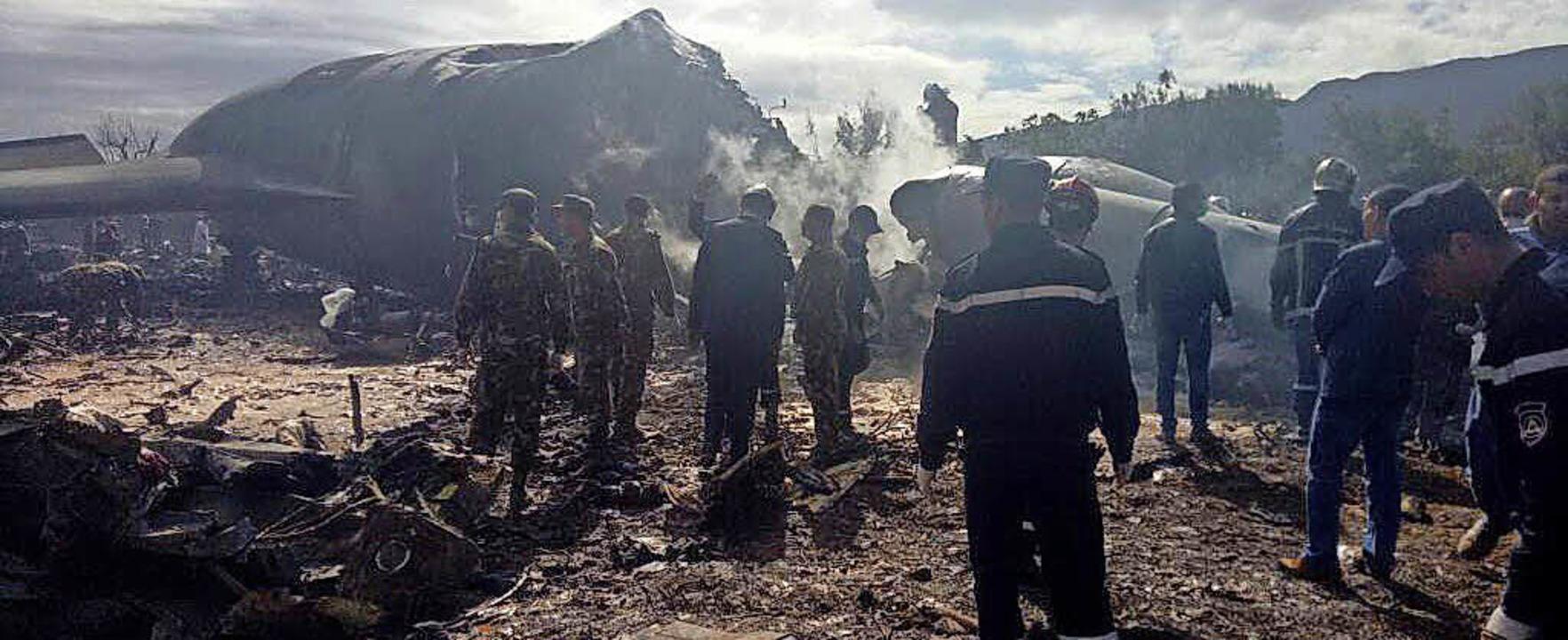 Feuerwehrleute stehen vor dem Wrack des abgestürzten Militärflugzeugs.   | Foto: dpa