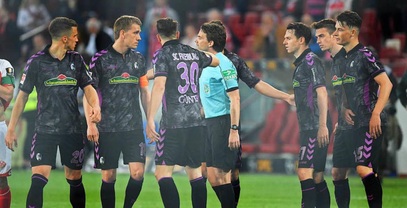 Schiedsrichter Guido Winkmann diskutie...Steinhaus mit den Freiburger Spielern.  | Foto: dpa