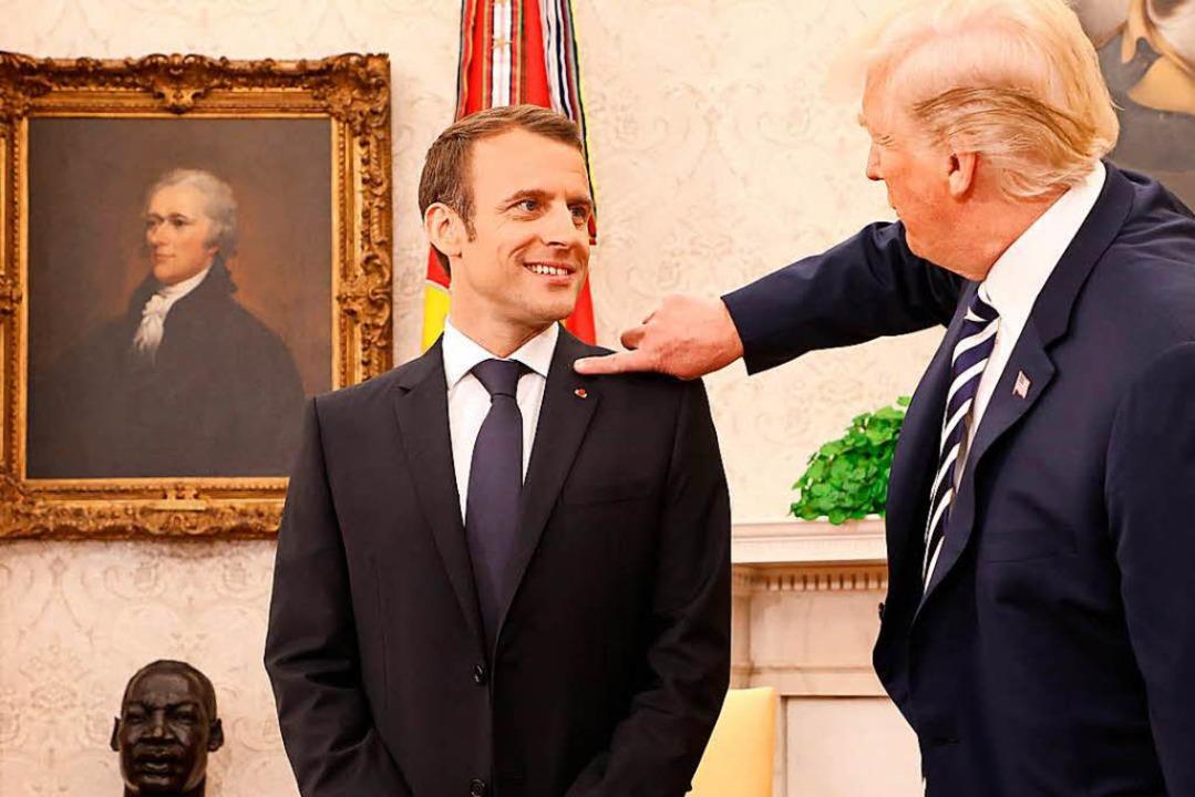 Zwischendurch wischt Trump dem Franzosen eine Schuppe von der Schulter.  | Foto: AFP