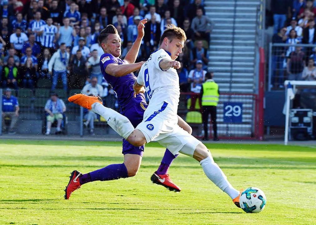 Der Karlsruher Marvin Pourie (r) und der Auer Nicolai Rapp kämpfen um den Ball.  | Foto: dpa