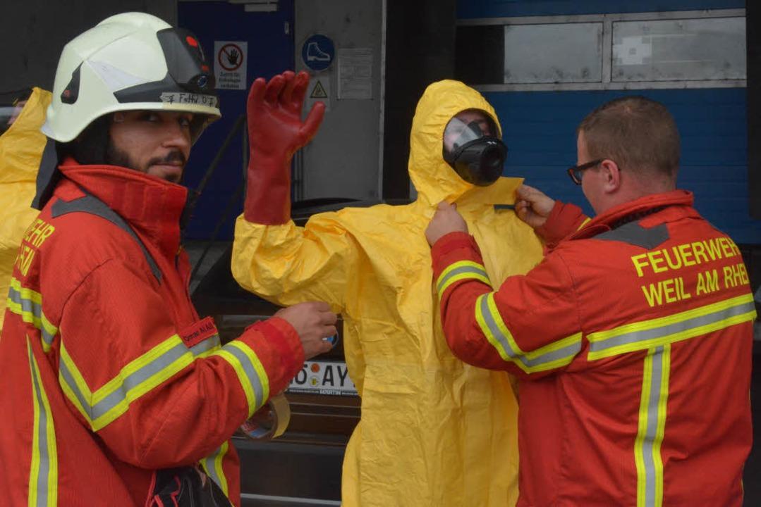 Feuerwehrleute helfen einem Kollegen, einen Vollschutzanzug anzulegen.  | Foto: Hannes Lauber