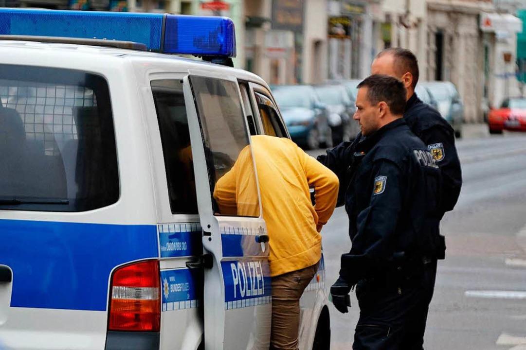 Beamte der Bundespolizei begleiten ein...n in Leipzig zu einem Polizeifahrzeug.  | Foto: dpa