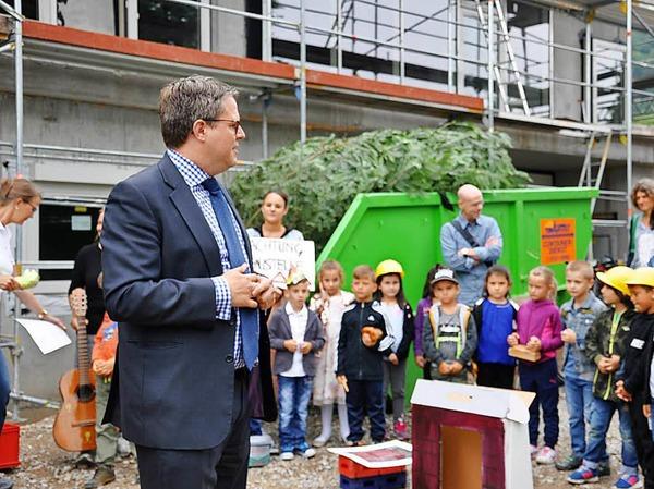 Bauarbeiter feiern gemeinsam mit Gemeinderäten, Verwaltung, Planern, Erzieherinnen und natürlich den Kindern Richtfest