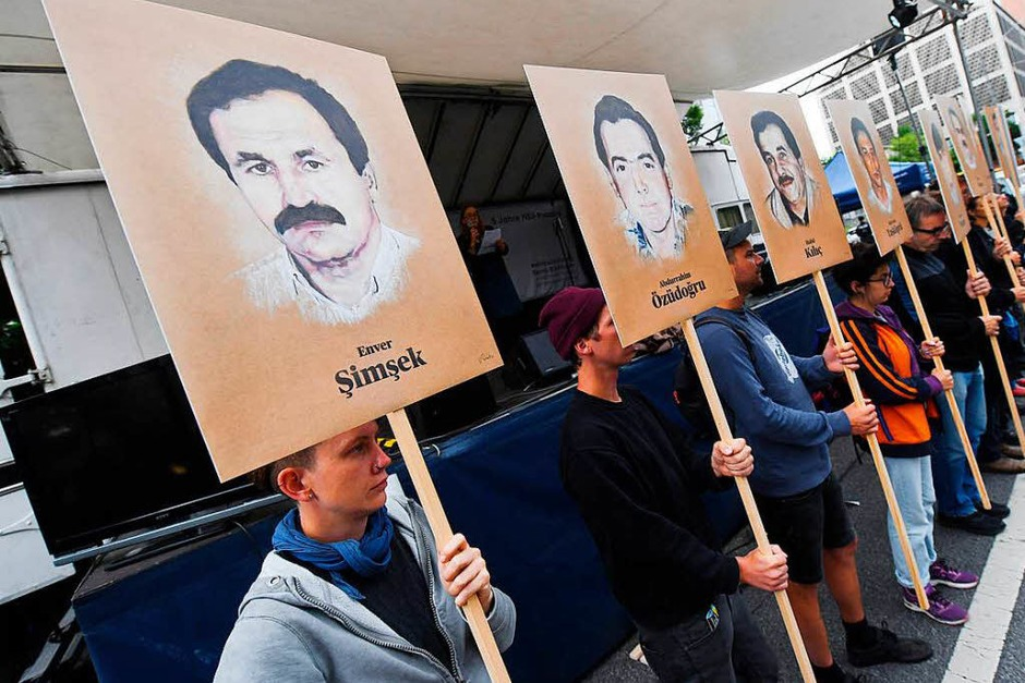 Demonstranten halten bei einer Kundgebung vor dem Oberlandesgericht Schilder mit Abbildung der NSU-Opfer. (Foto: dpa)