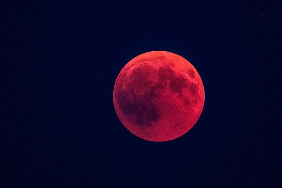 Gesehen bei Rottweil: Der Erdschatten schiebt sich über den rötlichen Vollmond. Bei der längsten Mondfinsternis des 21. Jahrhunderts tauchte der Mond in den Erdschatten ein. (Foto: dpa)