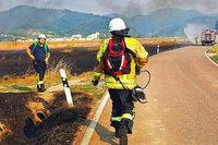 Feuerwehr löscht einen Brand auf Brachlandfläche