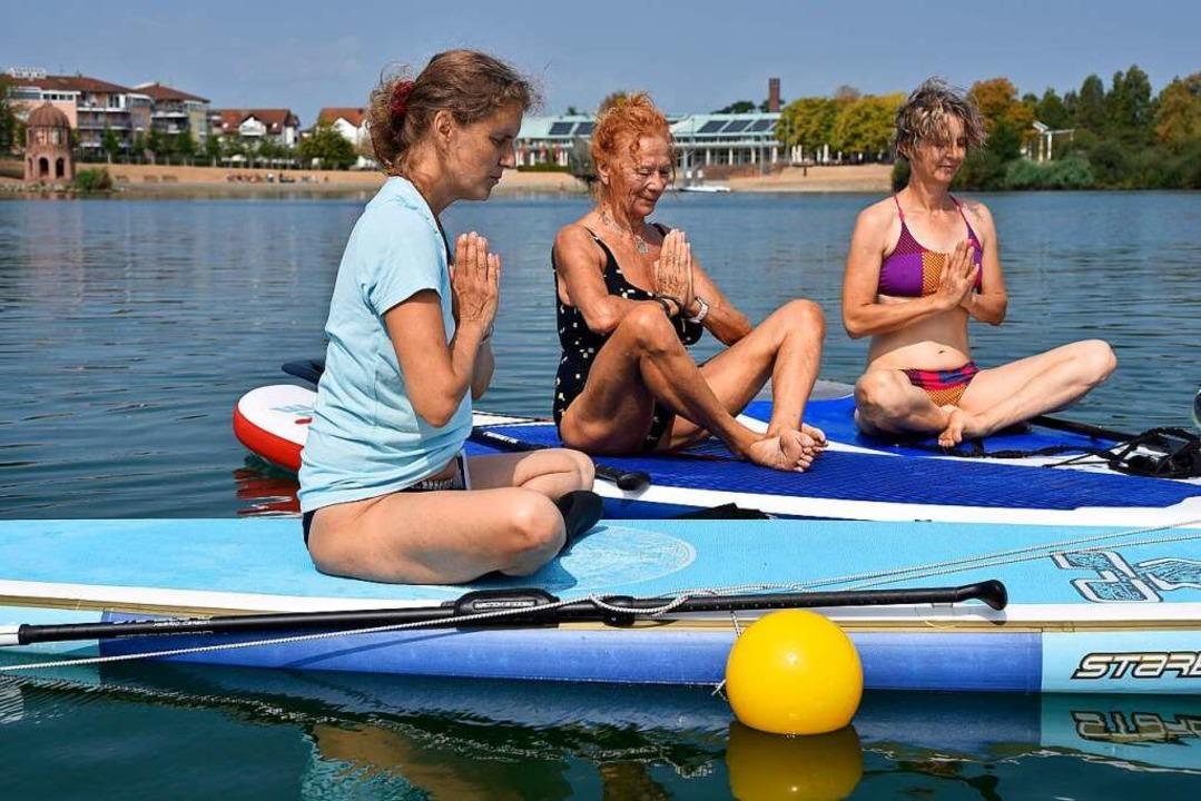 Lehrerin Sunita Koch (links mit T-Shir...ei einer Yoga-Übung auf dem Surfbrett.  | Foto: Thomas Kunz