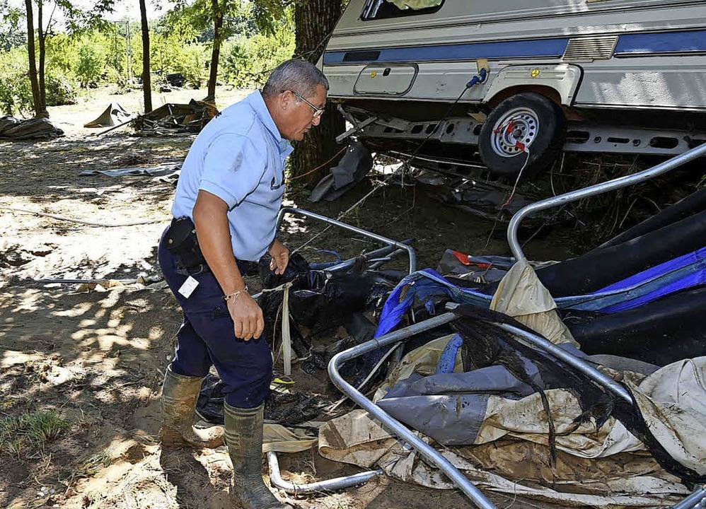 Ein Polizist untersucht einen der beschädigten Wohnwagen.   | Foto: dpa